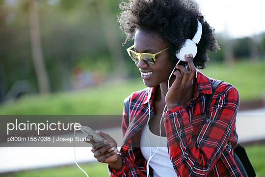 Portrait of happy young woman listening music with headphones and smartphone - p300m1587038 von Josep Suria