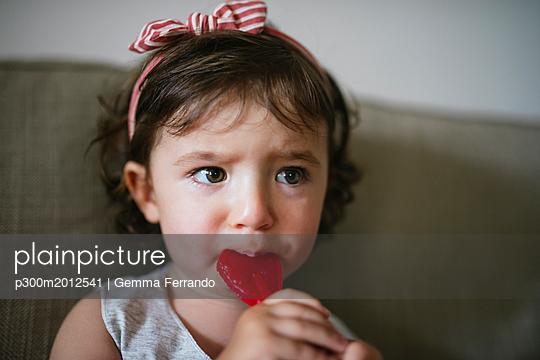 Cute baby girl eating a heart shaped lollipop at home - p300m2012541 von Gemma Ferrando