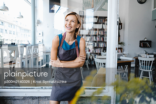 Business owner standing in front of her coffee shop - p300m2140326 by Kniel Synnatzschke