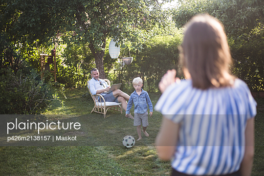 Father looking at son playing football with daughter at back yard - p426m2138157 by Maskot