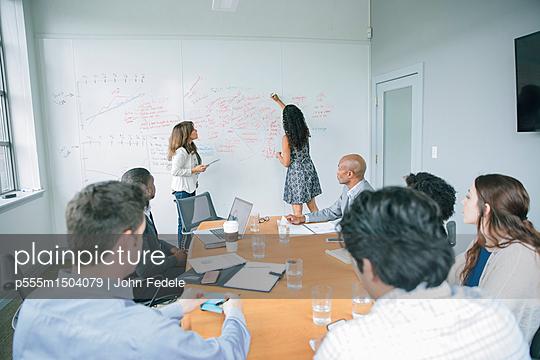 Businesswoman writing on whiteboard in meeting - p555m1504079 by John Fedele