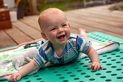 Portrait of baby boy on his blanket in the garden on a sunny day - p1047m1492568 by Sally Mundy