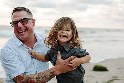 Cheerful father holding son at beach - p1166m1508299 by Cavan Images