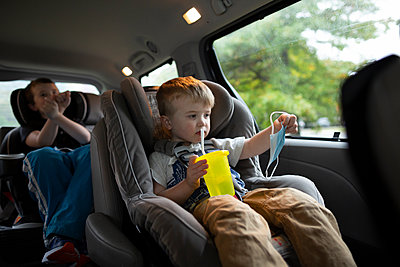 Two Brothers Sitting in Minivan Holding Up Face Mask During Pandemic - p1166m2218080 by Cavan Images