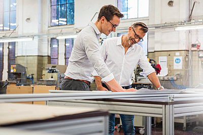 Two smiling businessmen in factory looking at plan - p300m1562629 by Daniel Ingold