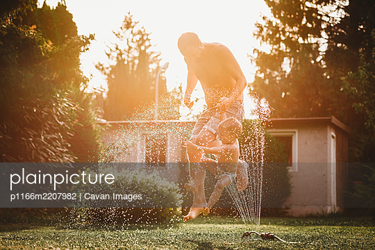 Father and child jumping over the water from the sprinkler in garden - p1166m2207982 by Cavan Images