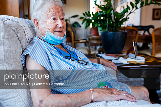 Female senior with protective mask sitting in armchair at home - p300m2213971 by Gemma Ferrando