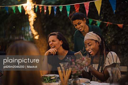 Cheerful multi-ethnic friends enjoying at table during dinner party in backyard - p426m2046200 by Maskot