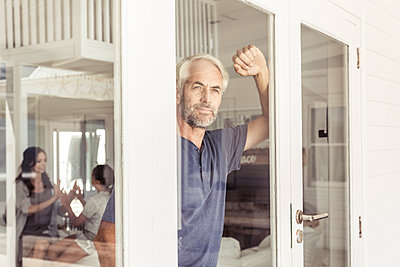 Portrait of mature man looking out of window - p300m2167033 by Floco Images