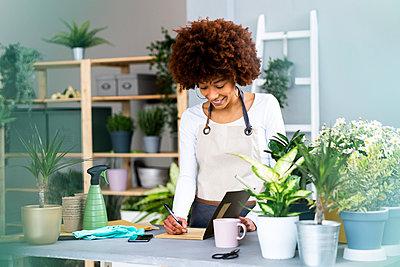 Afro woman gardening in a plant laboratory or shop, small business owner - p300m2287686 von Giorgio Fochesato
