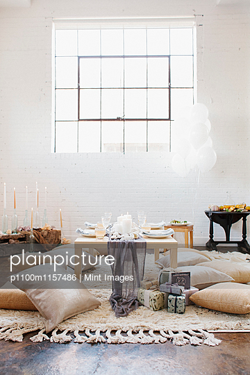 An apartment with a table set for a celebration meal. Cushions on the floor. - p1100m1157486 by Mint Images