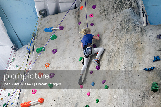 young girl climbing rock wall at indoor rock  climbing gym - p1166m2131449 by Cavan Images