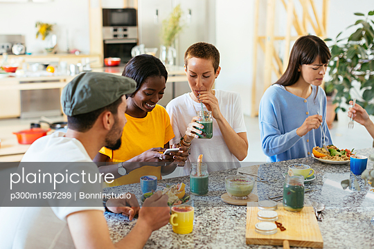 Friends sitting at kitchen counter eating and drinking - p300m1587299 von Bonninstudio