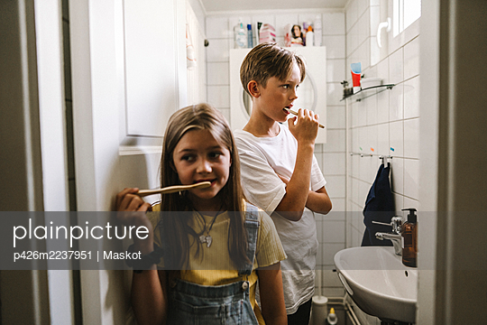 Brother and sister brushing teeth in bathroom - p426m2237951 by Maskot