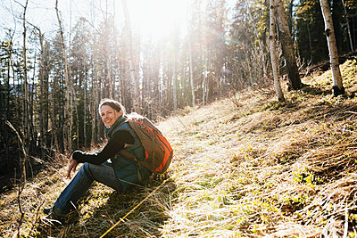 Portrait smiling, confident woman with backpack hiking in sunny woods - p1192m2094244 by Hero Images