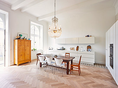 Modern kitchen with dining table in a refurbished old building - p300m1028947f by Dieter Schewig