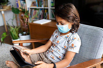 Boy with surgical mask sitting on armchair at home using digital tablet - p300m2189190 by Valentina Barreto