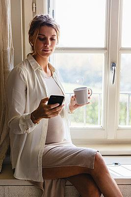 Pregnant woman using cellphone at the window. Lecco, Italy. - p300m2243193 von Michela Ravasio