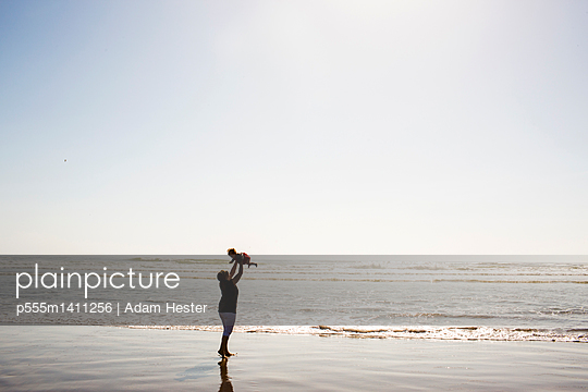 Caucasian mother lifting baby daughter on beach - p555m1411256 by Adam Hester