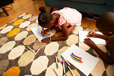 Girl drawing multicolor rainbow with markers on living room rug - p1023m2238487 by Himalayan Pics