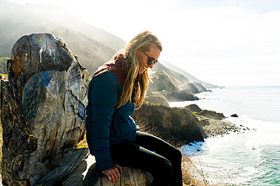 Side view of happy woman sitting on rock by sea - p1166m1210065 by Cavan Images