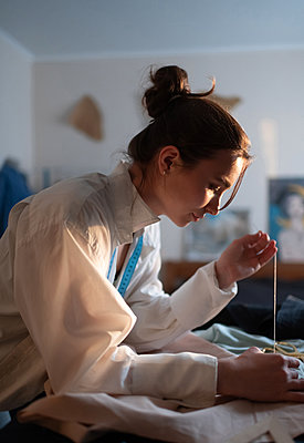 Focused female tailor creating clothes - p1166m2218576 by Cavan Images