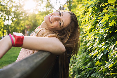 Happy young woman sitting on park bench - p1332m1589161 by Tamboly