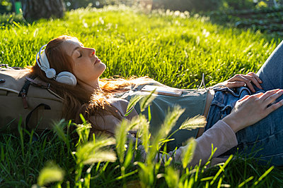 Young redheaded woman with headphones and smartphone in a park - p300m2113790 von VITTA GALLERY