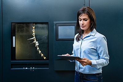 Businesswoman using tablet at a machine in a factory - p300m2188365 by Daniel Ingold