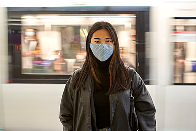 Young woman during pandemic with moving train in background - p300m2268287 by Veam
