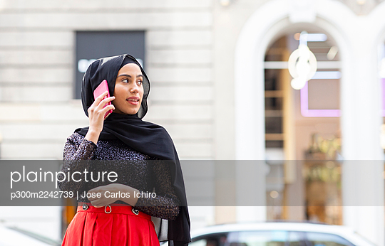 Portrait of young beautiful woman wearing black hijab talking on smart phone in middle of street - p300m2242739 by Jose Carlos Ichiro