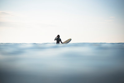 Asian Woman waiting for waves during sunrise summer surf session - p1166m2279619 by Cavan Images