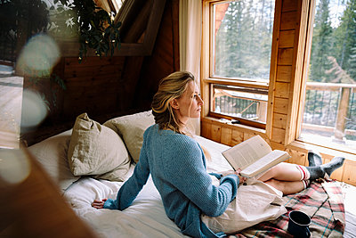 Serene woman reading book on cabin bed - p1192m2093948 by Hero Images