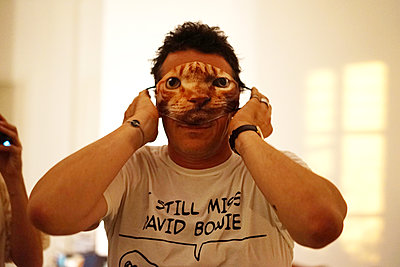 A man plays with a facial cloth mask at a party - p1610m2211232 by myriam tirler