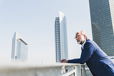 Serious mature businessman in the city looking around - p300m1587429 von Uwe Umstätter