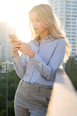 Blonde business woman checking smartphone on city rooftop - p300m2043122 by Steve Brookland
