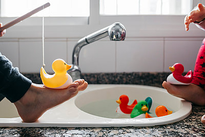 Crop view of boy and his little sister fishing rubber ducks in kitchen sink - p300m2189110 by Josep Rovirosa