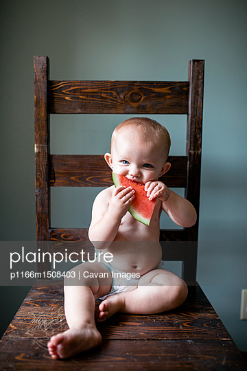 Portrait of shirtless baby girl eating watermelon while sitting on chair against wall at home - p1166m1508403 by Cavan Images