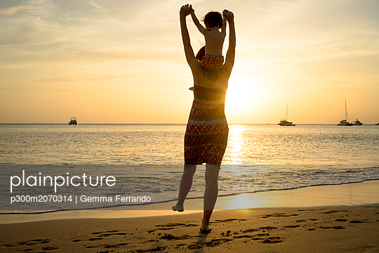 Thailand, Koh Lanta, back view of mother with baby girl on her shoulders at seashore during sunset - p300m2070314 by Gemma Ferrando