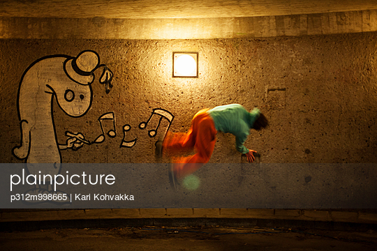 Man practicing parkour at night - p312m998665 by Kari Kohvakka