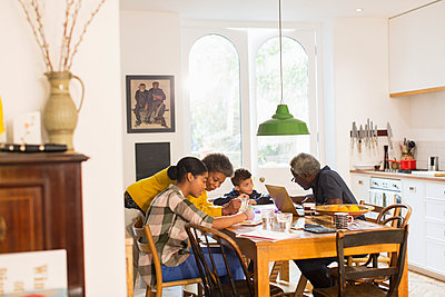 Grandparents helping grandchildren with homework at dining table - p1023m1583924 by Tom Merton