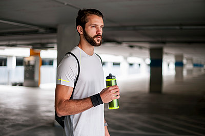 Athlete in parking garage holding drinking bottle - p300m1587383 by Daniel Ingold