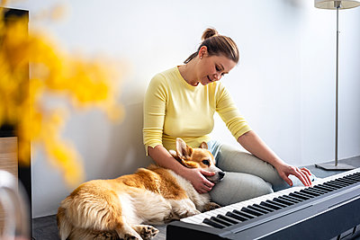 Mid adult woman practicing piano while dog relaxing on lap at home - p300m2282578 by Vasily Pindyurin
