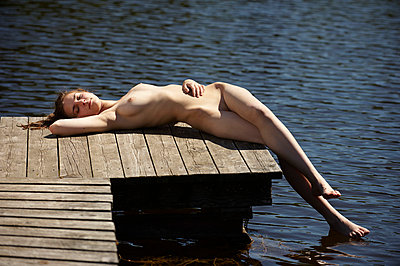 Woman sitting naked on a boardwalk - p5560165 by Wehner