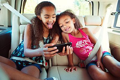 Sisters taking selfie while traveling in car - p1166m1225968 by Cavan Images