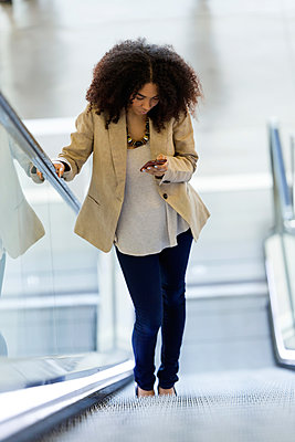 Young businesswoman using a smartphone on an escalator - p300m2121014 by Josep Suria