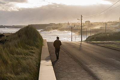 Rear view of man walking on a road at the coast, Sao Miguel Island, Azores, Portugal - p300m2179862 by VITTA GALLERY