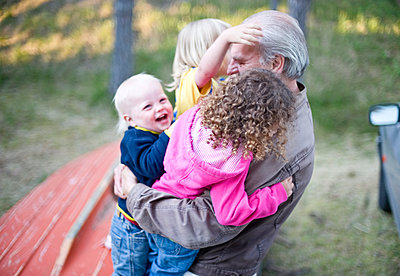 Grandfather playing with grandchildren - p312m1493638 by Rebecca Wallin