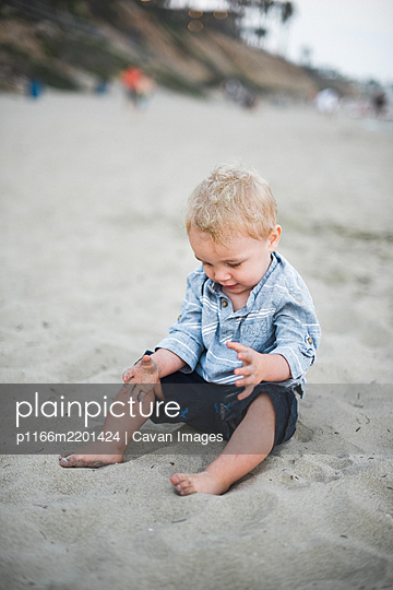 Little boy playing with sand on a California beach - p1166m2201424 by Cavan Images