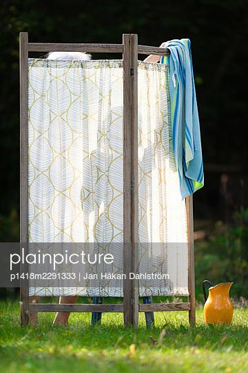 Woman washing outdoors behind screen - p1418m2291333 by Jan Håkan Dahlström